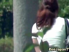 asian lady pees on tree