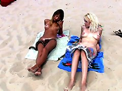 filming two sexy babes sunbathing on a beach completely naked