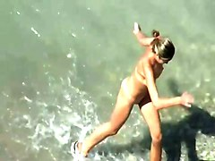 horny couple having sex in the water on a nudist beach