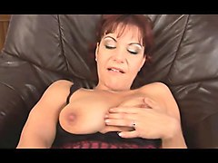 mature redhead masturbates solo on leather couch