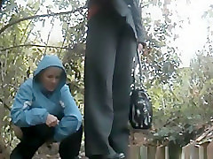 Chubby old woman caught pissing in the bushes