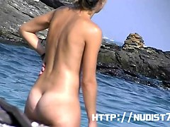 the beach nudist girl is lying on the beach
