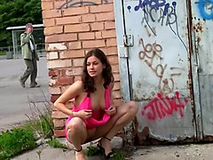 stunning busty teen babe in pink dress shows off her breasts on the street